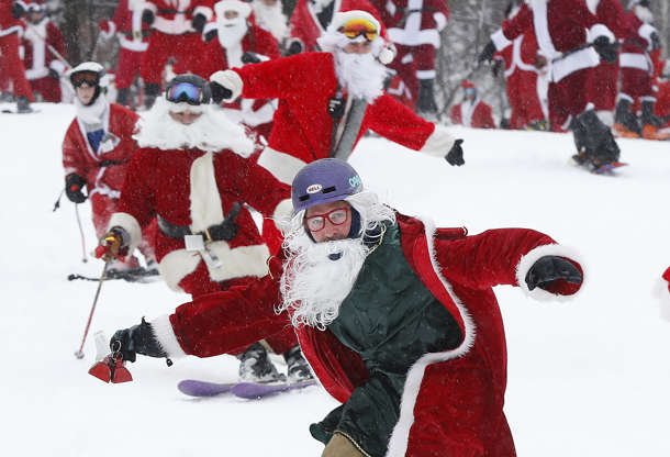 Slide 14 of 36: Skiers and snowboarders dressed as Santa Claus hit the slopes en masse during the annual Santa Sunday event, Sunday, Dec. 2, 2018, in Newry, Maine. The red-suited lookalikes aim to put a smile on people's faces while raising money for charity.