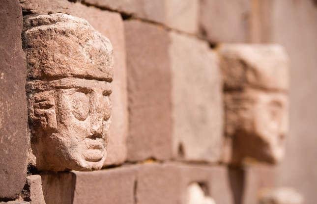Slide 5 de 23: A cidade pré-colombiana de Tiwanaku, na Bolívia, é objeto de muita controvérsia: ela foi fundada há 4 mil anos? Ou 8 mil anos? Ou 12 mil anos? Seria ela uma das cidades mais antigas do mundo? Ela tem, no mínimo, mil anos de idade. Desde o meio do platô no qual esse sítio está localizado, é possível admirar a estrutura e os detalhes ornamentais desse impressionante trabalho em pedra. Tiwanaku aparentemente foi lar de uma civilização antiga que estava bem à frente de seu tempo.