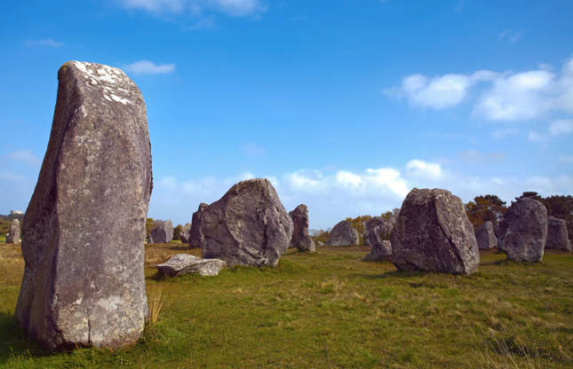 Slide 15 de 23: Encontradas na Britânia, as misteriosas pedras de Carnac têm cerca de 6 mil anos de idade. Por que 4 mil pedras teriam sido alinhadas em ordem decrescente de tamanho ao longo de cerca de 4 km?