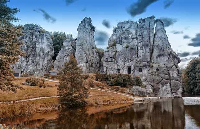 Slide 16 de 23: A Floresta de Teutoburgo, na Alemanha, abriga uma peça preciosa da história germânica. A Externsteine é uma formação de pedra que alguns creem ter sido usada como um sítio pagão de culto e observação solar. Esses pilares naturais de arenito se formaram milhões de anos atrás.
