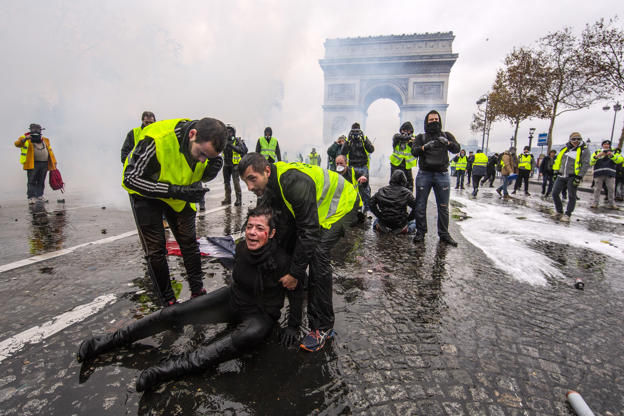 Slide 6 of 36: A protester is wounded by a water canon as they clash with riot police during a 'Yellow Vest' demonstration near the Arc de Triomphe on Dec. 1, in Paris, France.