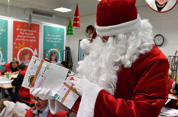 a man dressed as santa claus distributes letters to people in charge of answering letters addressed