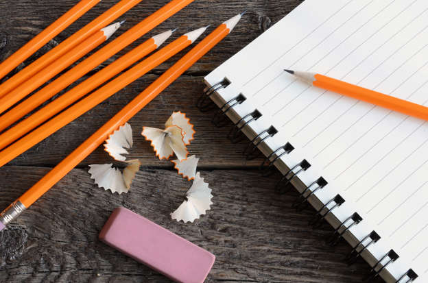 Slide 5 de 62: A top view image of several sharpened pencils and a opened notebook.