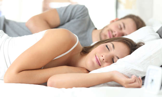 Slide 1 of 62: Happy couple sleeping in a comfortable bed at home