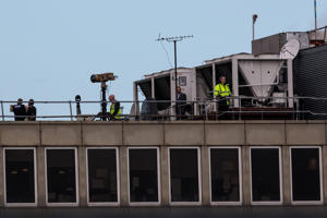 LONDON, ENGLAND - DECEMBER 21: Police officers and other people stand near equipment on the rooftop of a building as the runway is reopened at London Gatwick Airport on December 21, 2018 in London, England. Authorities at Gatwick have reopened the runway after drones were spotted over the airport on the night of December 19. The shutdown sparked a succession of delays and diversions in the run up to the Christmas getaway, in what authorities have called a 'deliberate act' to disrupt the airport. Police continue their search for the drone operators responsible.  (Photo by Jack Taylor/Getty Images)