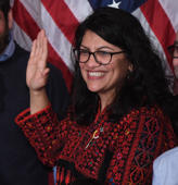 US House Representative Rashida Tlaib wearing a traditional Palestinian robe, takes the oath of office on Thomas Jefferson's English translated Quran