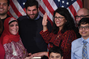 Rep. Rashida Tlaib, wearing a traditional Palestinian robe, takes the oath of office on Thomas Jefferson's English-translated Quran, with family members present at the U.S. Capitol on January 3, 2019.