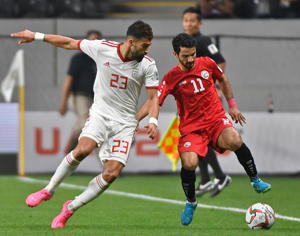 Iran's defender Ramin Rezaeian (L) fights for the ball with Yemen's forward Abdulwasea Al Matari (R) during the 2019 AFC Asian Cup Group D football match between Yemen and Iran at the Mohammed Bin Zayed stadium in Abu Dhabi on January 07, 2019.