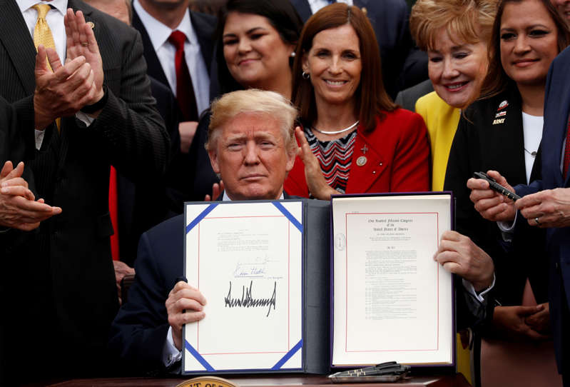 "U.S. President Donald Trump displays the ""VA (Veterans Affairs) Mission Act of 2018"" after signing it in the Rose Garden of the White House in Washington, U.S., June 6, 2018."