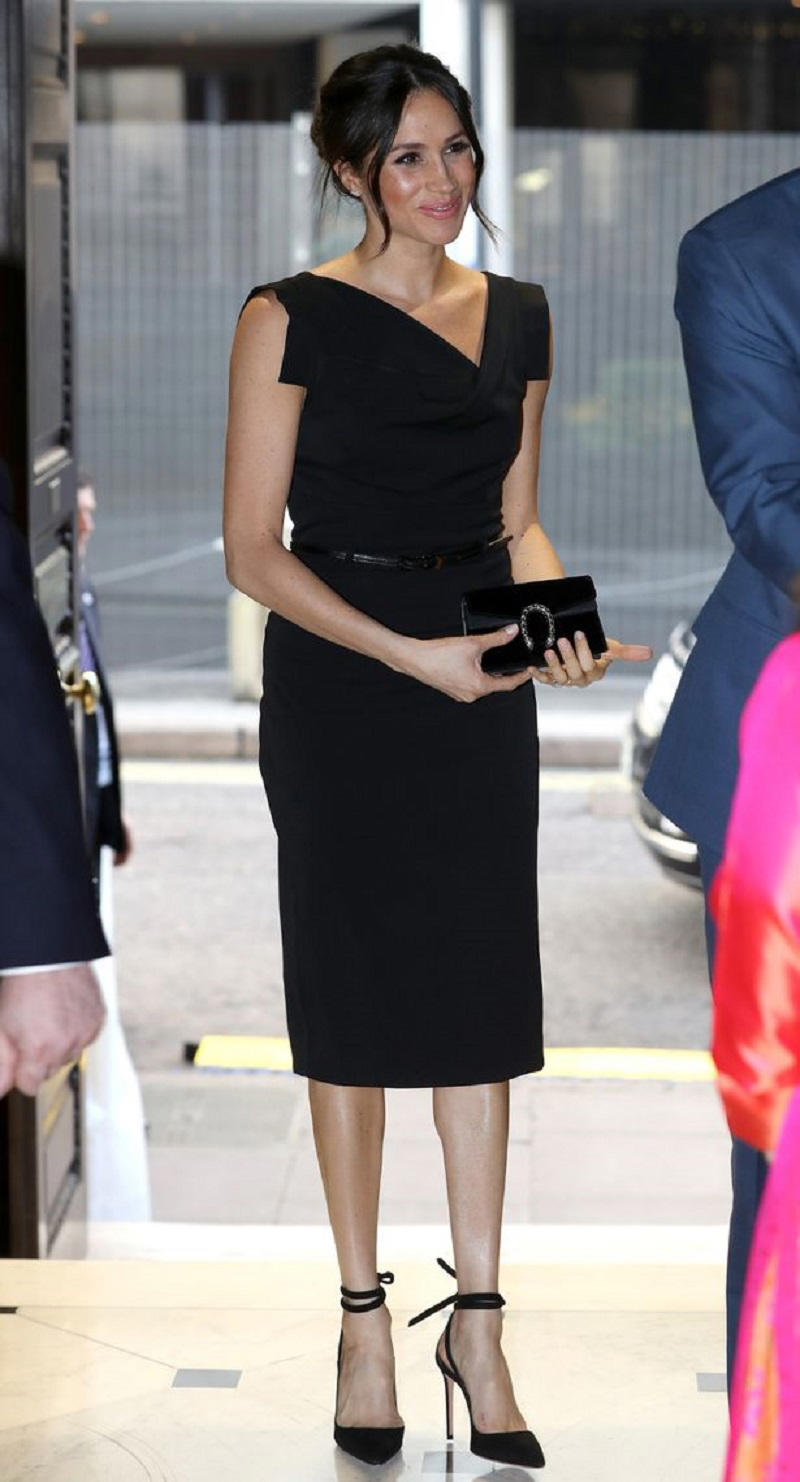 Meghan in stylish black Black Halo dress carrying a Gucci clutch and wearing a pair of Aquazurra ankle-strap heels (Image: Getty Images Europe)