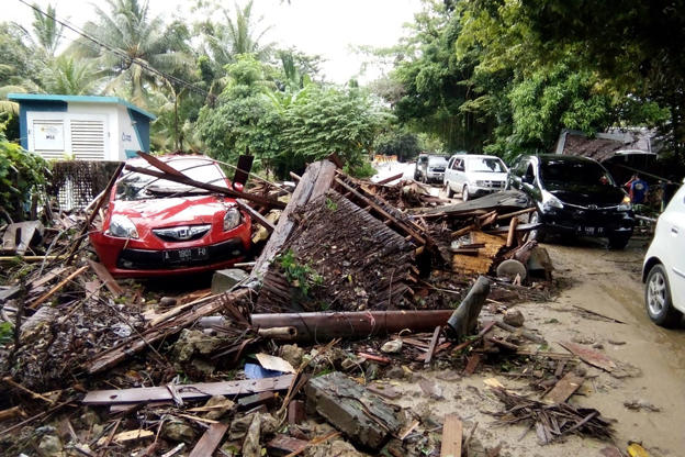 Slide 4 de 18: A damaged vehicle is seen amid wreckage from buildings along Carita beach on December 23, 2018, after the area was hit by a tsunami on December 22 following an eruption of the Anak Krakatoa volcano. - A tsunami following a volcanic eruption killed 62 people and injured hundreds more as it slammed without warning into tourist beaches and coastal areas around Indonesia's Sunda Strait on the night of December 22, sending panicked holidaymakers and residents fleeing. (Photo by Semi / AFP)        (Photo credit should read SEMI/AFP/Getty Images)