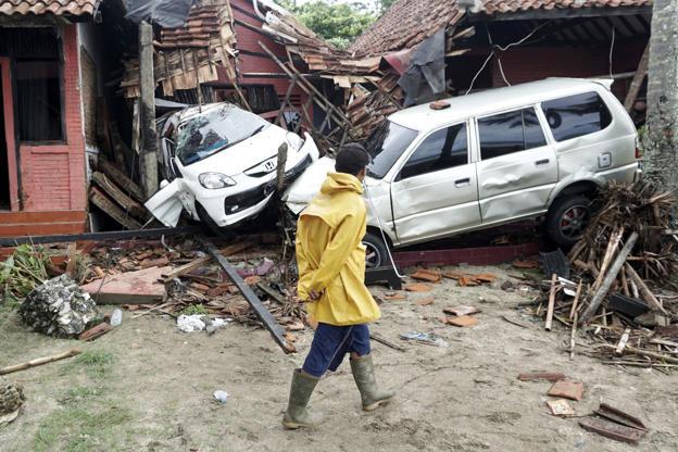 Slide 2 de 18: A villager walks past a car damaged by a tsunami, in Carita, Indonesia, Sunday, Dec. 23, 2018.