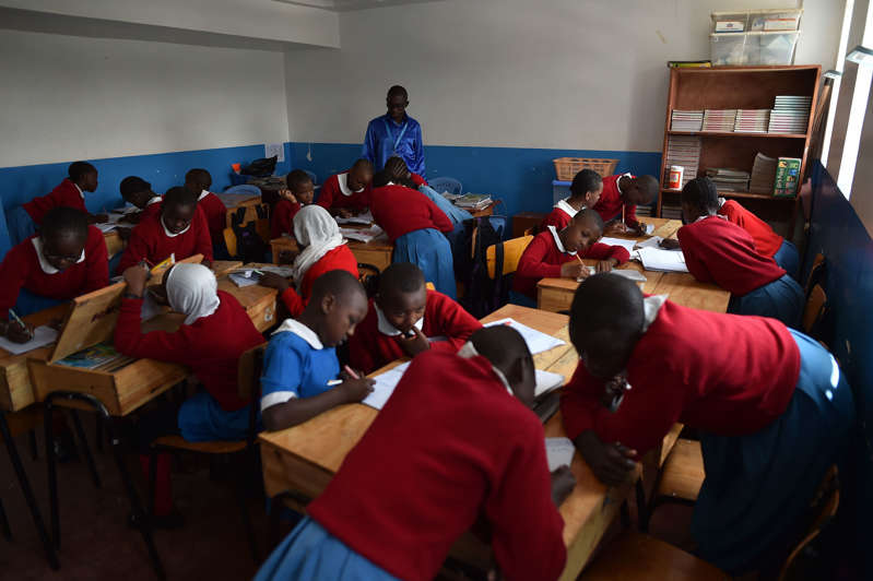 Pupils take part in a classroom exercise supervised by their teacher at a charity run primary school, Shining Hope for Communities, in the sprawling Kibera slum in the Kenyan capital, Nairobi, on January 16, 2018. / AFP PHOTO / TONY KARUMBA        (Photo credit should read TONY KARUMBA/AFP/Getty Images)