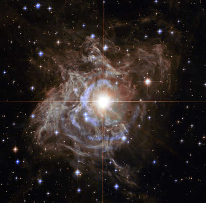 Slide 1 of 76: This Hubble image shows RS Puppis, a type of variable star known as a Cepheid variable. As variable stars go, Cepheids have comparatively long periods — RS Puppis, for example, varies in brightness by almost a factor of five every 40 or so days. RS Puppis is unusual; this variable star is shrouded by thick, dark clouds of dust enabling a phenomenon known as a light echo to be shown with stunning clarity. These Hubble observations show the ethereal object embedded in its dusty environment, set against a dark sky filled with background galaxies.