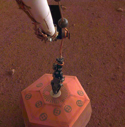 Slide 3 of 76: This set of images shows NASA's InSight lander deploying its first instrument onto the surface of Mars, completing a major mission milestone. InSight's robotic arm is white, with a black, handlike grapple at the end. The grapple is holding onto the copper-colored seismometer. The color-calibrated image was taken on Dec. 19, 2018, around dusk on Mars, with InSight's Instrument Deployment Camera (IDC), which is on the lander's robotic arm. JPL manages InSight for NASA's Science Mission Directorate. InSight is part of NASA's Discovery Program, managed by the agency's Marshall Space Flight Center in Huntsville, Alabama. Lockheed Martin Space in Denver built the InSight spacecraft, including its cruise stage and lander, and supports spacecraft operations for the mission. A number of European partners, including France's Centre National d'Études Spatiales (CNES) and the German Aerospace Center (DLR), are supporting the InSight mission. CNES and the Institut de Physique du Globe de Paris (IPGP) provided the Seismic Experiment for Interior Structure (SEIS) instrument, with significant contributions from the Max Planck Institute for Solar System Research (MPS) in Germany, the Swiss Institute of Technology (ETH) in Switzerland, Imperial College and Oxford University in the United Kingdom, and JPL. DLR provided the Heat Flow and Physical Properties Package (HP3) instrument, with significant contributions from the Space Research Center (CBK) of the Polish Academy of Sciences and Astronika in Poland. Spain's Centro de Astrobiología (CAB) supplied the wind sensors.