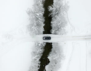 TOPSHOT - An aerial view shows a car crossing a bridge as the street is snow covered on January 9, 2019 in Untertauern, Austria. (Photo by HELMUT FOHRINGER / APA / AFP) / Austria OUT        (Photo credit should read HELMUT FOHRINGER/AFP/Getty Images)
