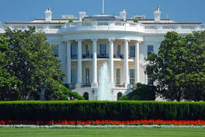 a large white building with White House in the background: 