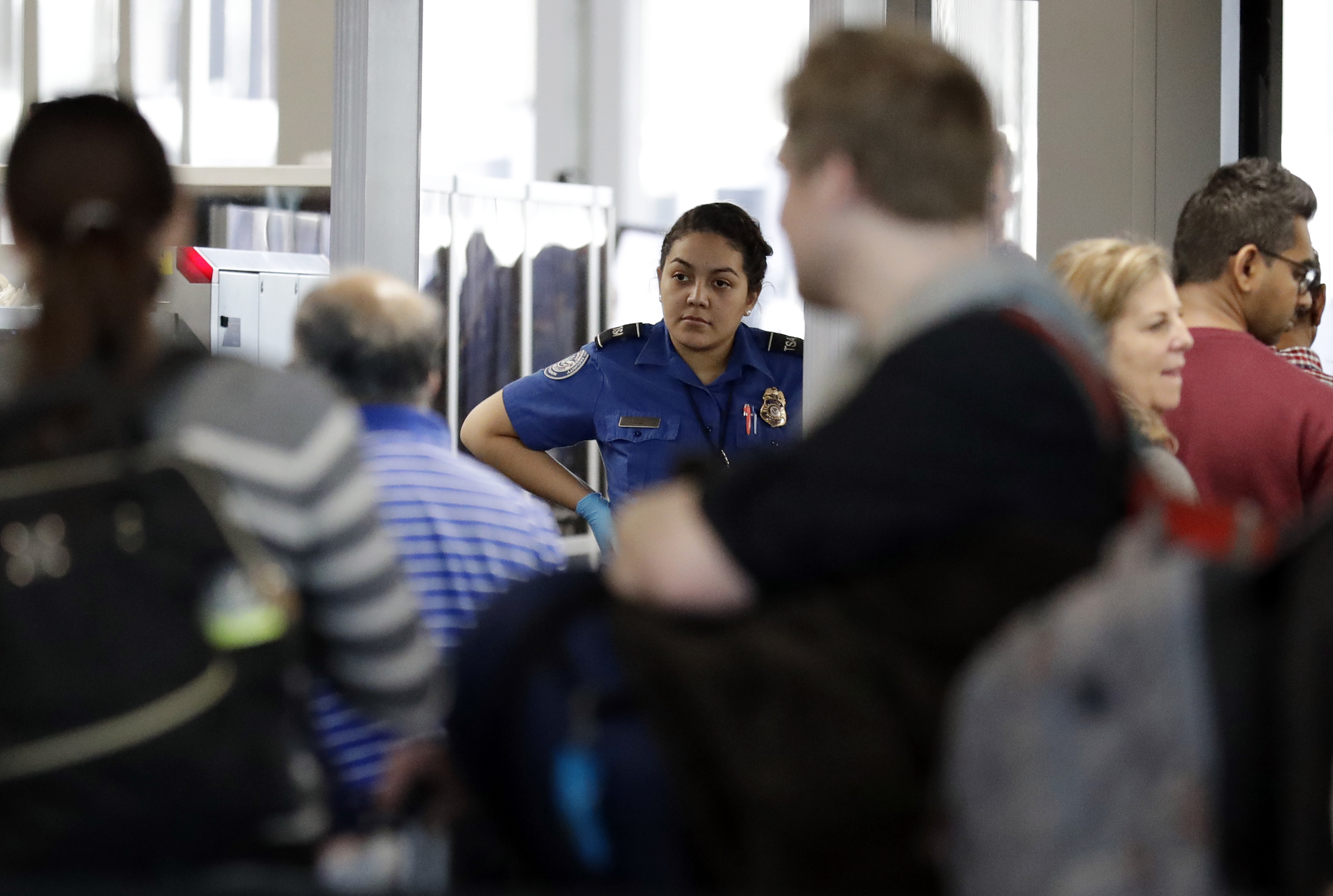 A TSA worker works at O'Hare International Airport in Chicago, Tuesday, Dec. 25, 2018. TSA is working through the holidays without pay. (AP Photo/Nam Y. Huh)