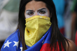 An anti-government protester covers her face with a Venezuelan flag, and uses toothpaste around her eyes to help lessen the effect of tear gas, during clashes with security forces after a rally demanding the resignation of President Nicolas Maduro in Caracas, Venezuela, Wednesday, Jan. 23, 2019. The head of Venezuela's opposition-run congress declared himself interim president at the rally, until new elections can be called.