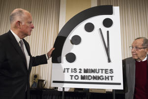 Former California Gov. Jerry Brown, left, and former Secretary of Defense William Perry unveil the Doomsday Clock during The Bulletin of the Atomic Scientists news conference in Washington, Thursday, Jan. 24, 2019.  The Doomsday Clock is set at two minutes to Midnight. (AP Photo/Cliff Owen)