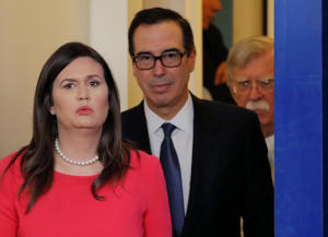 White House Press Secretary Sarah Huckabee Sanders leads U.S. Treasury Secretary Steven Mnuchin and National Security Advisor John Bolton into the press briefing room to announce the Trump administration's economic sanctions against Venezuela and the Venezuelan state owned oil company Petroleos de Venezuela (PdVSA) at the White House in Washington, U.S., January 28, 2019. REUTERS/Jim Young