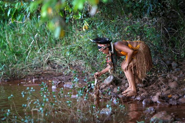 Slide 4 de 75: Índia da tribo Pataxo Ha-ha-hae segura peixe morto próximo ao rio Paraopeba