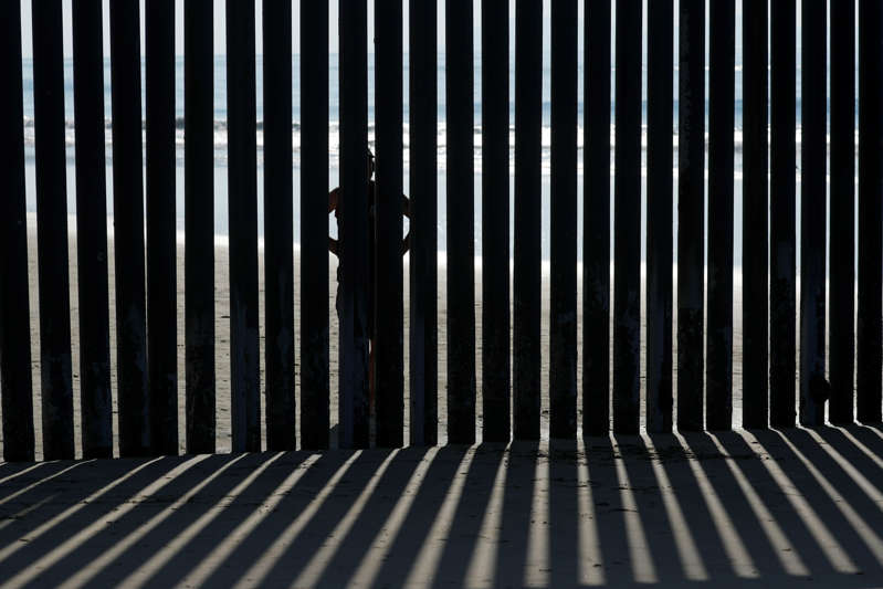 A person looks through the border wall towards the United States at Border Field State Park in San Diego, California, U.S. November 20, 2018.   REUTERS/Mike Blake
