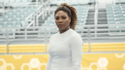Serena Williams standing in front of a fence