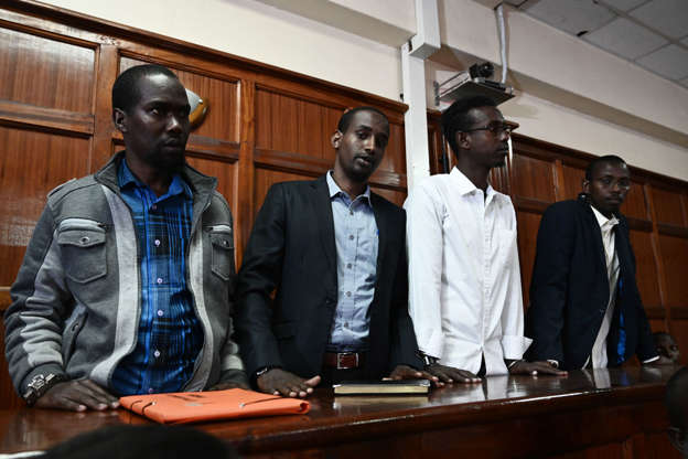 Suspects charged with helping al Qaeda-linked militants launch an attack on the Westgate mall, Liban Abdullah Omar and Mohamed Ahmed have their handcuffs loosened as they stand in the dock while co-accused Hussein Hassan and Adan Mohamed look on during the appearance for their case at the Milimani Law Courts in Nairobi, Kenya December 20, 2018.
