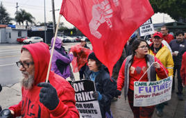 Spanish teacher at Hamilton High School, Jose Ramos, left, joins teachers during a strike in front of Hamilton High School in Los Angeles on Wednesday, Jan. 16, 2019. Los Angeles school administrators urged the union to resume bargaining as tens of thousands of teachers planned to walk picket lines for a third day Wednesday, after being joined on strike for the first time by some of their counterparts from independent charter schools. (AP Photo/Richard Vogel)