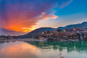 Dusk time at Rishikesh, holy town and travel destination in India. Colorful sky and clouds reflecting over the Ganges River.