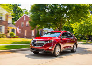 a red car driving down a street: 2019 Chevrolet Equinox