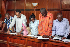 (L-R) Osman Ibrahim, Guleid Abdihakim, Gladys Kaari Justus, Oliver Muthee and Joel Nganga, six suspects arraigned in court in connection with an Islamist attack on a Nairobi hotel complex that left 21 dead, stand in the courthouse of Nairobi, on January 18, 2019. - A magistrate granted a request from the prosecution to detain the four men and one woman for 30 days while investigations continue. The suspects are accused of 'possible involvement' in the almost 20-hour siege of the DusitD2 hotel and office complex by a suicide bomber and four gunmen who were killed by security forces, a court document said. (Photo by STRINGER / AFP)        (Photo credit should read STRINGER/AFP/Getty Images)