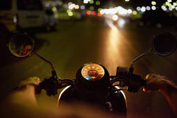 POV shot of a man riding a motorbike at night