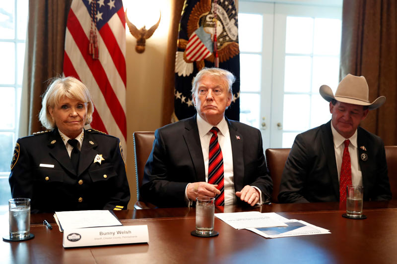 """President Donald Trump, with Carolyn """"Bunny"""" Welsh, sheriff of Chester County, Pa., left, and AJ Louderback, sheriff of Jackson County, Texas, attends a roundtable discussion on border security with local leaders, Friday Jan. 11, 2019, in the Cabinet Room of the White House in Washington."""