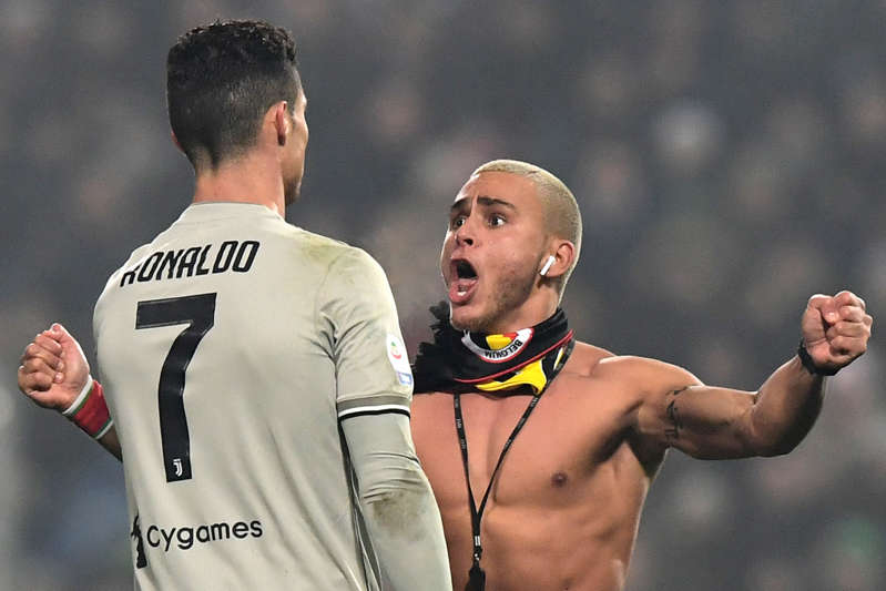 A spectator (R) who emerged on the pitch goes to Juventus' Portuguese forward Cristiano Ronaldo during the Italian Serie A football match Sassuolo vs Juventus on February 10, 2019
