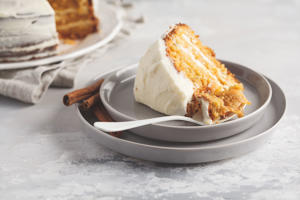 Piece of carrot homemade cake with white cream on a gray background. Festive dessert concept.