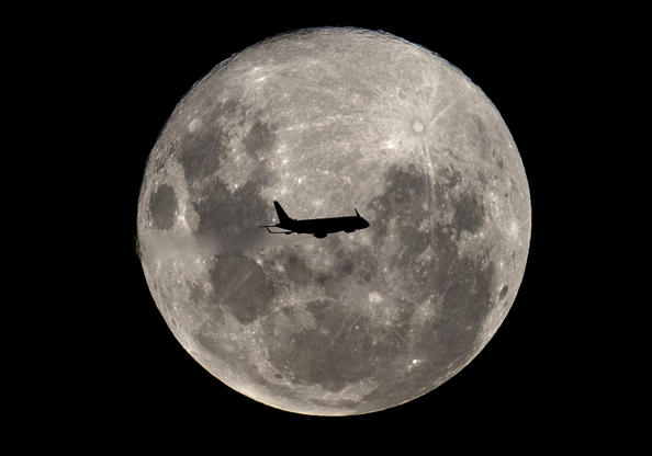 Slide 4 de 31: An Embraer 190-100IGW plane (registration LV-CKZ) of Aerolineas Argentinas, on a regular flight from Buenos Aires to the Argentine city of Bahia Blanca, passes in front of the 'Supermoon' as seen from Buenos Aires on February 19, 2019. (Photo by Alejandro PAGNI / AFP)        (Photo credit should read ALEJANDRO PAGNI/AFP/Getty Images)