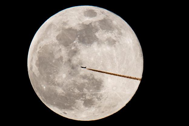Slide 11 de 31: 19 February 2019, Bavaria, Nürnberg: A plane flies by before the full moon. Photo: Daniel Karmann/dpa (Photo by  via Getty Images)