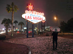 A photographer uses an umbrella to protect his camera from snow as he takes photos at the Welcome to Fabulous Las Vegas sign during a winter storm on February 20, 2019 in Las Vegas, Nevada. The National Weather Service in Las Vegas issued a winter weather advisory for the area overnight.