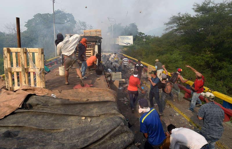 Ao menos duas pessoas morreram, uma delas um adolescente de 14 anos, e 31 ficaram feridas, em distúrbios registrados na fronteira entre a Venezuela e o Brasil
