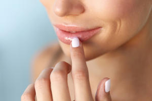 Lip Protection. Closeup of Beautiful Young Woman Healthy Lips. Female Model Smiling Mouth With Smooth Perfect Skin And Natural Manicure Touching Her Plush Lips. Lip Care And Beauty. High Resolution