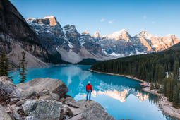 Man looking at Moraine lake at sunrise, Banff National Park, Alberta, Canada