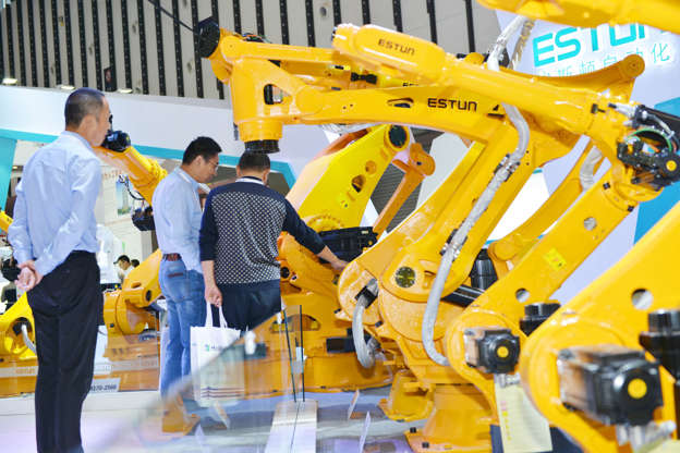 NANJING, CHINA - OCTOBER 11: People look at Estun industrial robots during the 2018 World Intelligent Manufacturing Summit at the Nanjing International Expo Center on October 11, 2018 in Nanjing, Jiangsu Province of China. The 2018 World Intelligent Manufacturing Summit with the theme of 'empowering the future through intelligent manufacturing' is held on October 11-13 in Nanjing. (Photo by VCG/VCG via Getty Images)