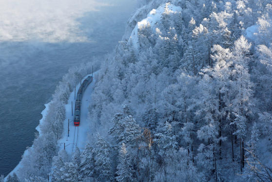 Slide 1 of 83: A passenger train moves along the bank of the Yenisei River in the Siberian Taiga forest covered with snow and hoarfrost outside Krasnoyarsk, Russia February 11, 2019. REUTERS/Ilya Naymushin