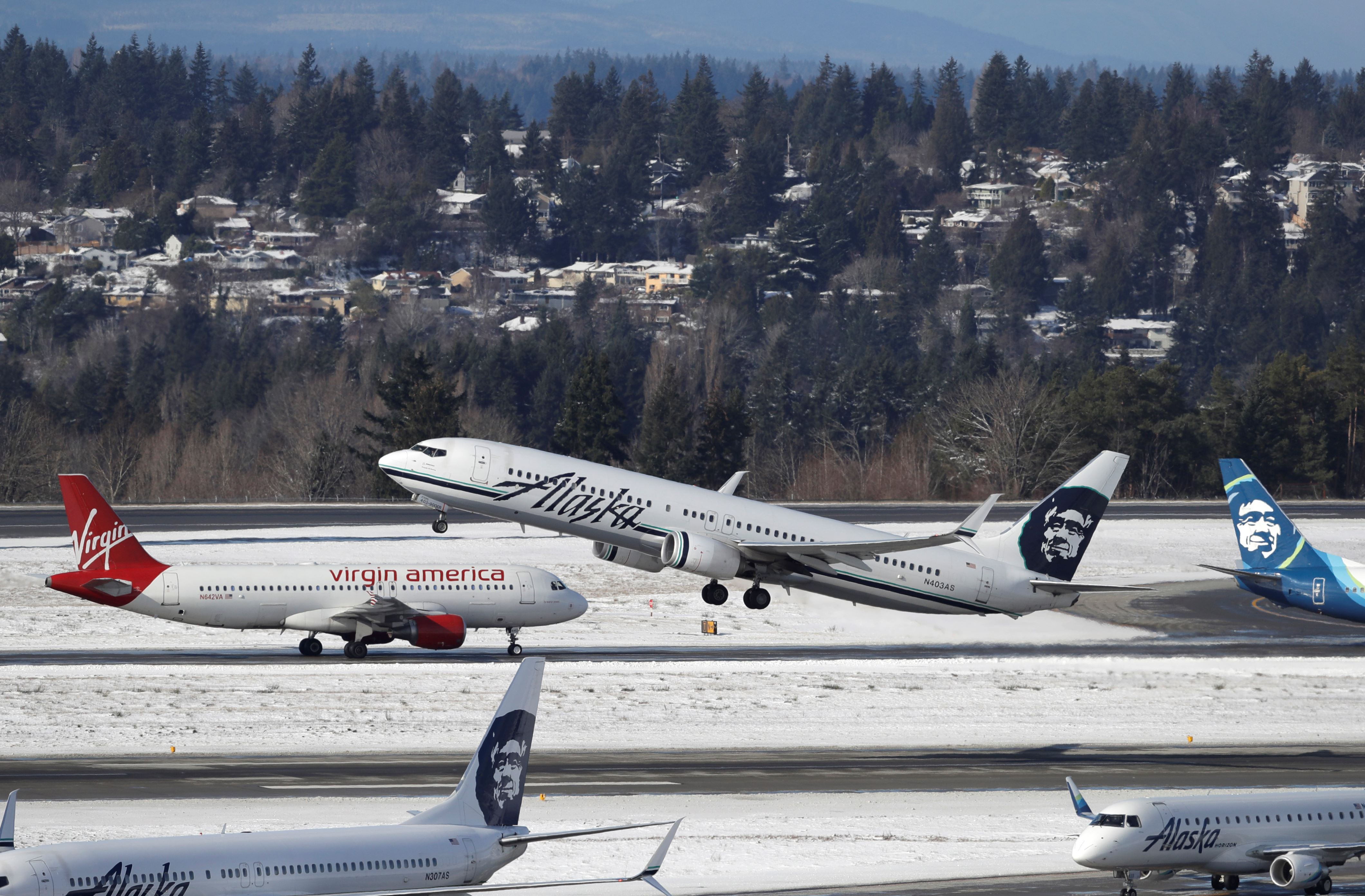 An Alaska Airlines plane takes off above a taxiing Virgin America plane, Tuesday, Feb. 5, 2019, on a snow-bordered runway at Seattle-Tacoma International Airport in Seattle. (AP Photo/Ted S. Warren)