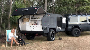 a truck is parked in front of a car: Bruder EXP-4 camping trailer