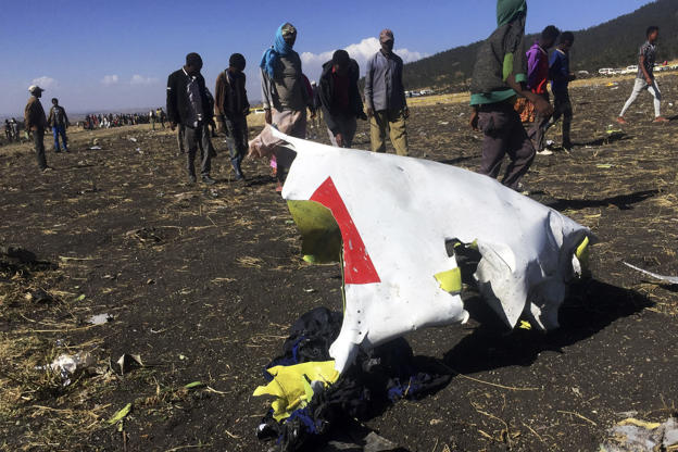 Slide 1 of 18: People walk past a part of the wreckage at the scene of the Ethiopian Airlines Flight ET 302 plane crash, near the town of Bishoftu, southeast of Addis Ababa, Ethiopia March 10.