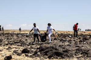 Rescue team carry collected bodies in bags at the crash site of Ethiopia Airlines near Bishoftu, a town some 60 kilometres southeast of Addis Ababa, Ethiopia, on March 10, 2019. - An Ethiopian Airlines Boeing 737 crashed on March 10 morning en route from Addis Ababa to Nairobi with 149 passengers and eight crew believed to be on board, Ethiopian Airlines said. (Photo by Michael TEWELDE / AFP)        (Photo credit should read MICHAEL TEWELDE/AFP/Getty Images)