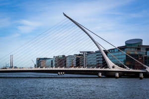 Cityscape sea view of the modern white Samuel Beckett harp bridge in Dublin in the foreground and office buildings in the background.